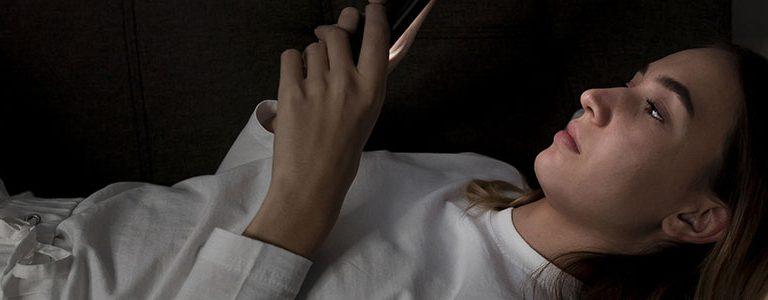 femme dans son lit regardant son téléphone mobile